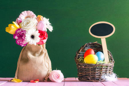 Photo for Easter card with a bouquet of flowers in a jute bag and a wicker basket with painted eggs and a wooden banner, on a pink table and a green wall. - Royalty Free Image