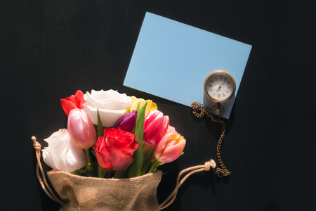 Photo for Colorful bouquet of diverse flowers in a jute bag, a vintage pocket watch and a blank blue message card, on a black background. - Royalty Free Image