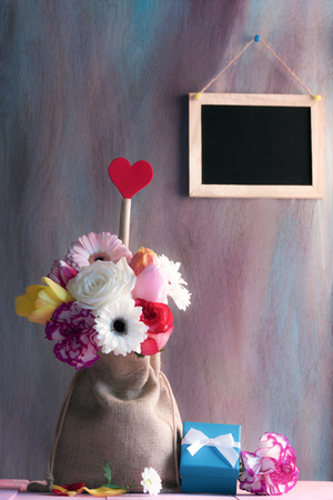 Photo for Mother day card with colorful flowers and a red heart shape in a hessian bag, a blue gift box on a pink table and a chalkboard on the purple wall. - Royalty Free Image