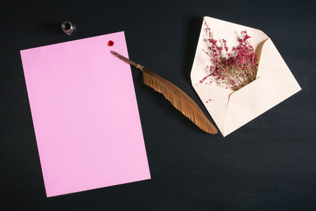 Photo for Open envelope full with red flowers, an antique feather pen on a pink paper note with a red ink splash on a black wooden background. - Royalty Free Image