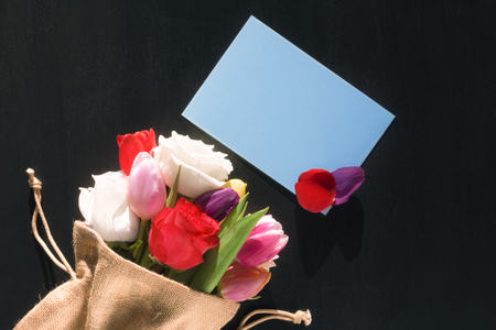 Photo for Colorful bouquet of diverse flowers wrapped in a jute sack and a blank blue paper note with flower petals on it, on a black background. - Royalty Free Image