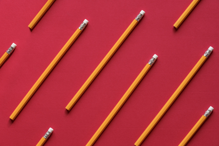 Photo for Education background concept with a bunch of yellow wooden pencils arranged symmetrically, like a pattern on a red paper sheet. - Royalty Free Image