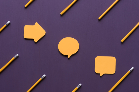 Photo for Unwritten yellow  notes in different shapes placed on a purple wooden background, surrounded by yellow wooden pencils. - Royalty Free Image