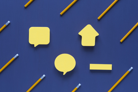 Photo for Yellow sticky notes in different sizes and shapes, with place for text, placed on a blue wooden background, surrounded by yellow wooden pencils. - Royalty Free Image