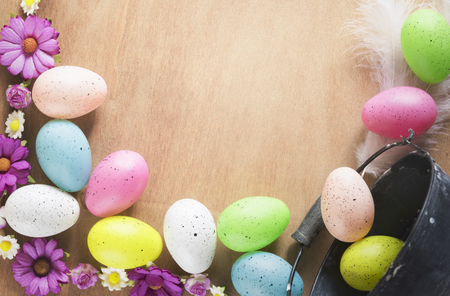 Photo for Easter frame design with a bunch of multicolored painted eggs, colorful spring flowers and feathers, displayed on a table with space for text. - Royalty Free Image