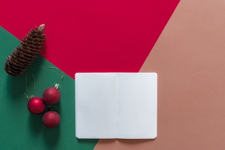 Photo for Christmas concept in a minimal style with a white empty notebook, red Christmas balls, and a pine cone, on a red, green and orange background. - Royalty Free Image