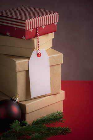 Photo for Xmas gifting image with a stack of gift boxes, an unwritten etiquette, fir twig, and a red Christmas ball, on a red background. - Royalty Free Image