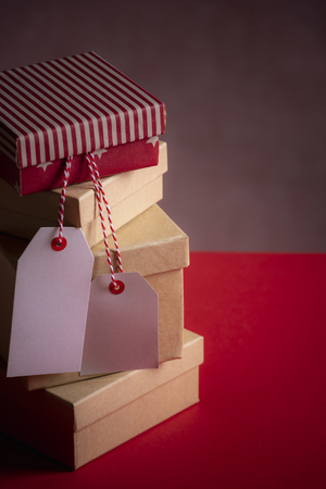 Photo for Greeting card idea with a bunch of gift boxes, stacked on top of each other and two unwritten tags, on a red background. Gifting concept. - Royalty Free Image