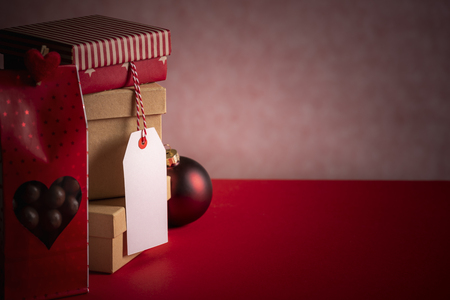 Photo for Christmas gifting theme image with a pile of gift boxes, a red candy bag, an unwritten tag, and an Xmas ball, on a red background. - Royalty Free Image