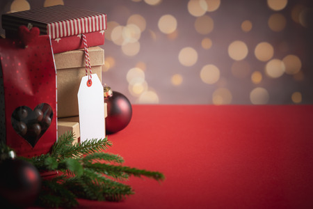 Photo for Xmas gifting concept with a stack of gift boxes with an unwritten label, a red bag of candy, Christmas decorations, and bokeh lights. - Royalty Free Image