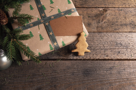 Photo for Gift wrapped in classic brown paper and green trees design, fir twigs, Christmas tree shaped gingerbread cookie and a blank tag, on a rustic table. - Royalty Free Image