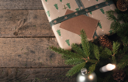 Photo for Green fir twigs, pine cones, and Christmas balls, near a gift wrapped in classic brown paper with trees, and a lit candle, on a vintage wooden table. - Royalty Free Image