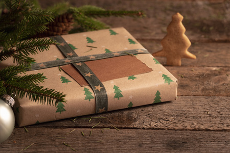 Photo for Gift box wrapped in brown classic paper and Christmas trees design, fir twigs, Xmas ball, and a Christmas tree cookie, on a rustic table. - Royalty Free Image