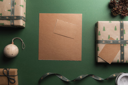 Photo for Unwritten vintage brown paper on a green background, surrounded by Christmas presents and decorations. - Royalty Free Image