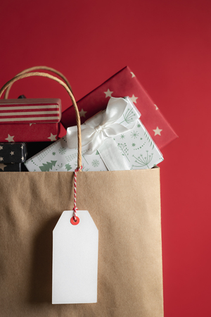 Photo for Classic brown paper bag with a blank tag hanging, full of different colored gifts. - Royalty Free Image