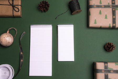 Photo for Above view of two unwritten notebooks on a green background, surrounded by Christmas gifts and decorations. - Royalty Free Image