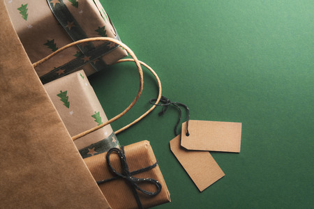 Photo for Christmas gifts, wrapped in classic brown paper, dropping from an overturned paper bag and two unwritten labels tied to the handle. - Royalty Free Image