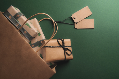 Photo for Brown paper bag full of presents, with two empty tags, overturned on a green background, spreading gifts wrapped in classic paper. - Royalty Free Image