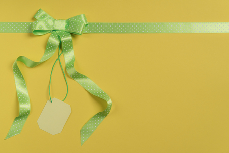 Photo for High angle view of a gift wrapped in yellow paper, with green ribbon and bow and a blank tag. Shopping discount concept. Gifting context. - Royalty Free Image