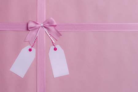 Photo for Above view of a gift frame, with pink bow and ribbon and two empty labels hanging from the bow. Greeting card concept. - Royalty Free Image