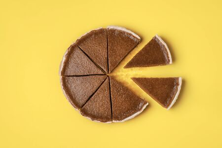 Photo for Pie slices separated from the whole pumpkin pie on a yellow background.  Flat lay of traditional American pie. Minimal Thanksgiving food. Sweet pastry - Royalty Free Image