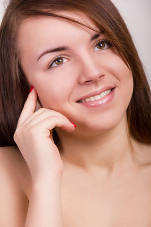 Natural portrait of a beautiful young woman with brown straight hair and clean skin without makeup