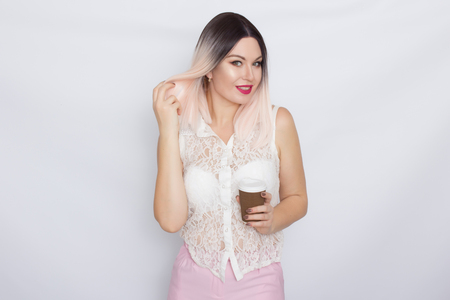 Photo for Cheerful pretty blonde woman in white shirt and pink pants with a cup of coffee over white background - Royalty Free Image