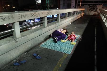 Foto de Homeless woman and a child sleeping in the street of Bangkok, Thailand - Imagen libre de derechos