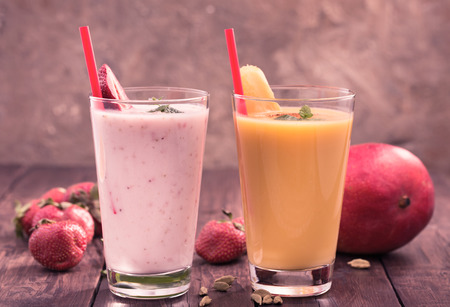 Foto de Strawberry and mango smoothies on old wooden table - Imagen libre de derechos