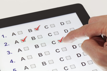 Photo pour Finger clicking on a tablet with multiple-choice questions - image libre de droit