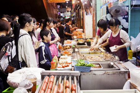 Photo pour Hong Kong, China - November 16, 2011: Food vendors in Mong Kok, Hong Kong, selling street food for take away. These vendors offer some great street food, including fish balls, octopus legs, pig skin, red sausage. - image libre de droit