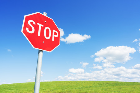 Photo pour Stop road sign against blue sky and green field - image libre de droit