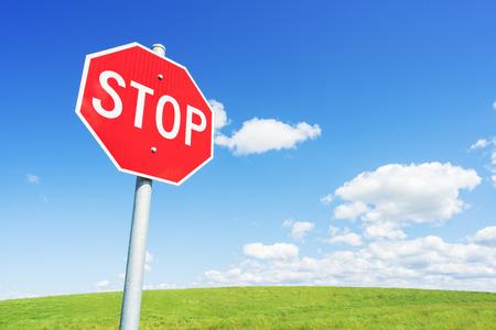 Foto de Stop road sign against blue sky and green field - Imagen libre de derechos