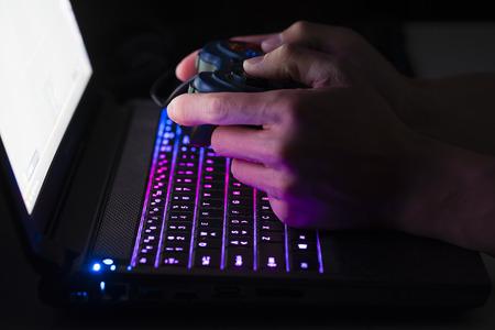 Photo pour Playing computer game on laptop with joypad - image libre de droit