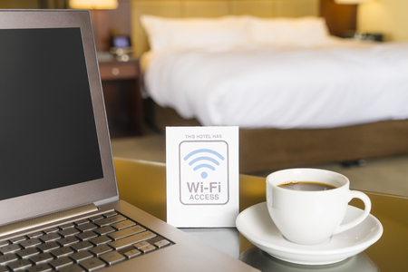 Photo for Hotel room with wifi access sign, laptop and cup of coffee - Royalty Free Image