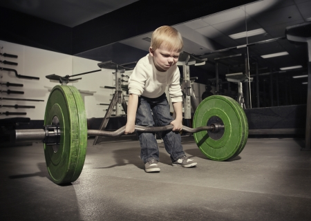 Photo pour Determined young boy trying to lift a heavy weight bar - image libre de droit