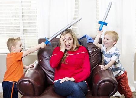 Foto de Young Mother overwhelmed by her kids - Imagen libre de derechos