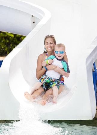 Photo for Family fun on the water slide at a waterpark - Royalty Free Image