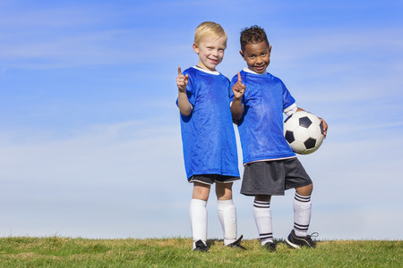 Photo pour Two diverse young soccer players showing No. 1 sign. Full length view of two youth recreation league soccer players - image libre de droit