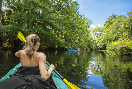 Foto de Woman kayaker paddling down a beautiful jungle river with two people in a canoe on a gorgeous day. Lots of copy space and view from behind - Imagen libre de derechos