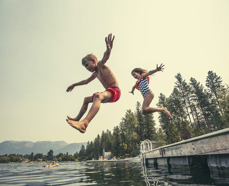 Foto de Kids jumping off the dock into a beautiful mountain lake. Having fun on a summer vacation at the lake with friends - Imagen libre de derechos