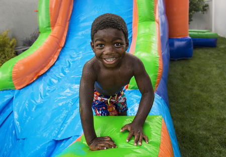 Photo for Smiling little boy sliding down an inflatable bounce house - Royalty Free Image