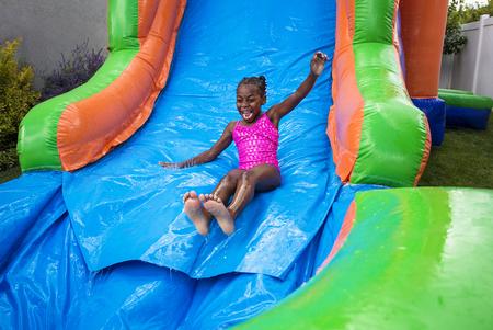 Foto de Happy little girl sliding down an inflatable bounce house - Imagen libre de derechos