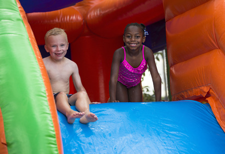 Photo for Happy kids sliding down an inflatable bounce house - Royalty Free Image