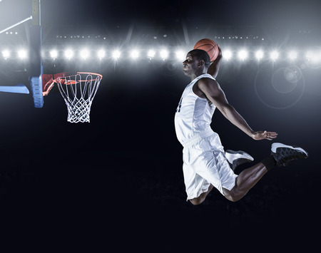 Photo pour Basketball Player scoring a slam dunk basket - image libre de droit