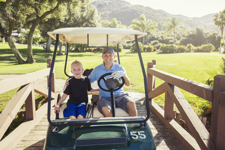 Photo for Father and son golfing together on a Summer day riding in a golf cart together - Royalty Free Image