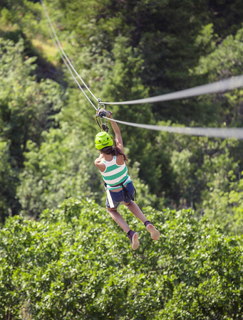 Photo for Teen girl riding a zip line through the forest. View from behind - Royalty Free Image