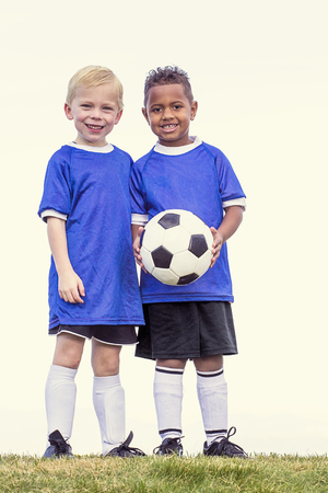 Full length view of two youth recreation league soccer players. Two diverse little boys standing on a grass field