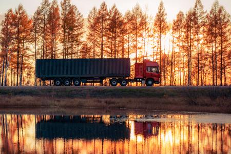 Foto de Red truck on a road at sunset. Focus on container - Imagen libre de derechos