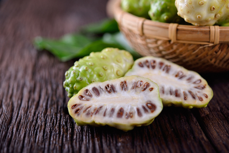Photo for whole and half cut fresh noni fruit with leaf on wooden background - Royalty Free Image